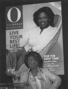 Oprah Winfrey steht vor dem Cover der Premierenausgabe von 0, the Oprah Magazine. 0 erschien erstmals im April 1999. Reproduziert mit Genehmigung von AP/Wide World Photos.